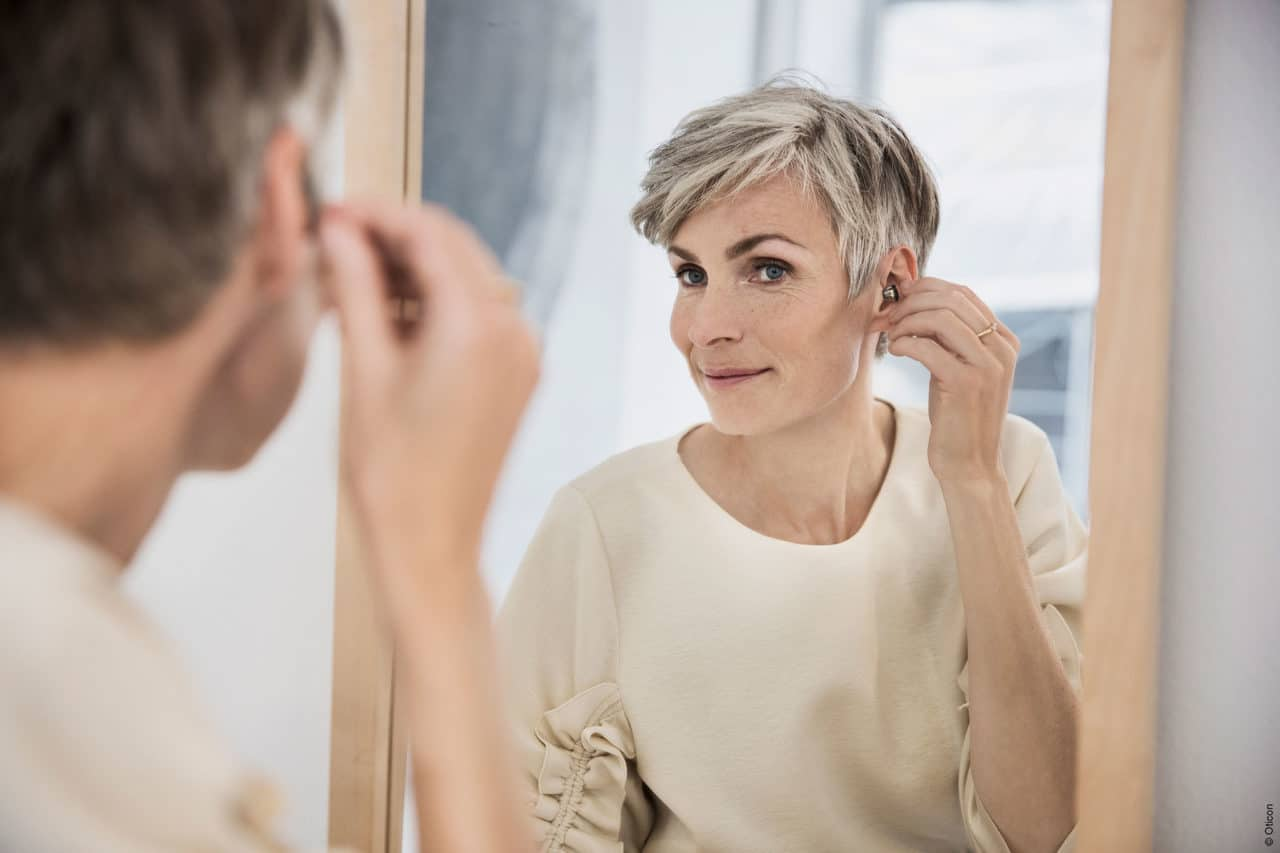 A patient adjusting their hearing aid in the mirror