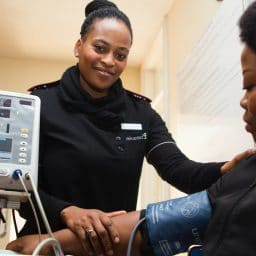 A female Nurse checking a woman's blood pressure