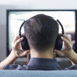 Back side of a man wearing black headphones in front of blurry out-of-focus television and home entertainment system background