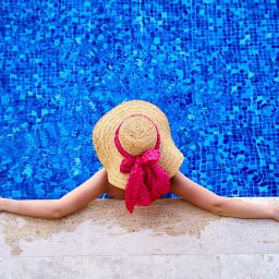 Birds eye view of a woman sitting in a pool with a sunhat