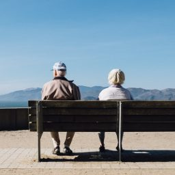 Two seniors sit on bench