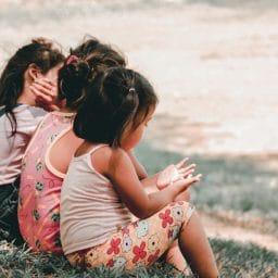 Children sit together outside.