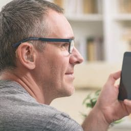 Man with a hearing aid and smartphone