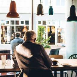 Older man sitting down inside a coffee shop.